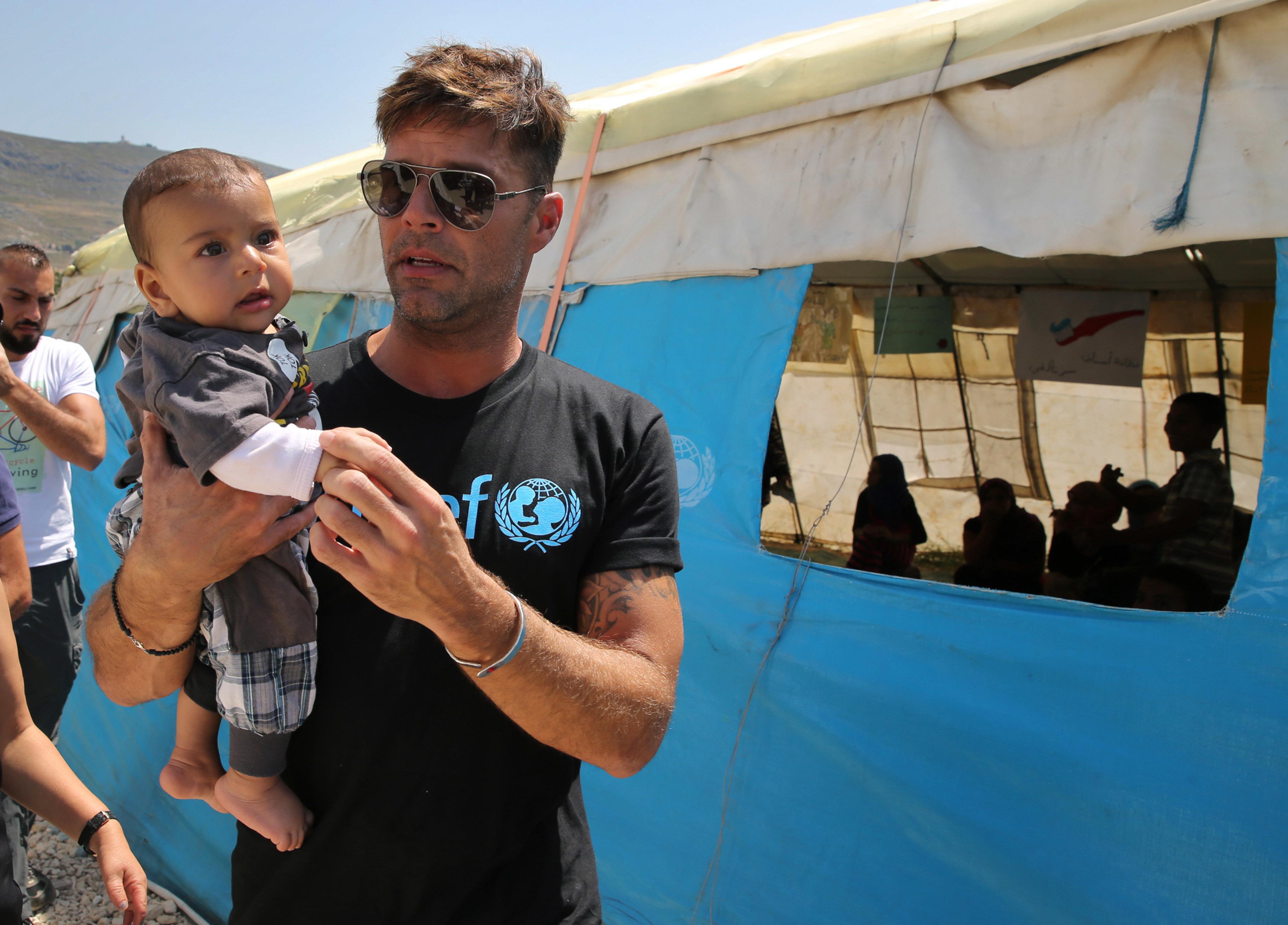"""En esta foto del jueves 2 de junio del 2016, Ricky Martin visita a niños sirios en un campamento informal de refugiados sirios en Minnieh, cerca de la ciudad norteña de Tripoli, en el Líbano. El superastro puertorriqueño, embajador de buena voluntad de UNICEF, dijo que la palabra """"refugiado"""" a perdido valos y que la comunidad internacional debería """"abrir su corazón"""". (AP Foto/Hussein Malla)"""