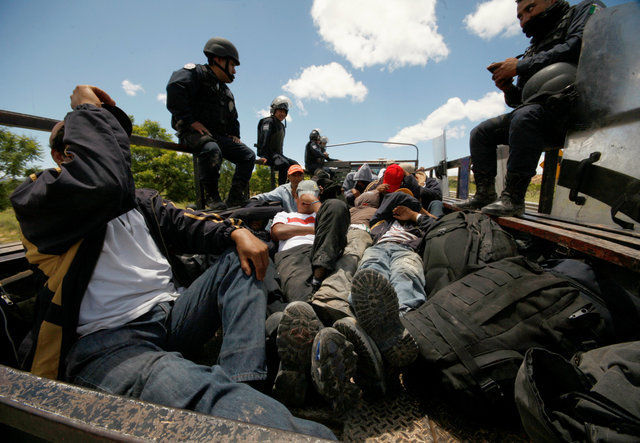 Riot police officers keep watch next to protesters from the National Coordination of Education Workers (CNTE) teachers' union, who were detained after clashing with the police during a protest against President Enrique Pena Nieto's education reform, in the town of Nochixtlan, northwest of the state capital, Oaxaca City, Mexico June 19, 2016. REUTERS/Jorge Luis Plata FOR EDITORIAL USE ONLY. NO RESALES. NO ARCHIVES.
